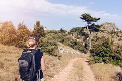 Young woman with backpack at mountain trail. Royalty Free Stock Photo
