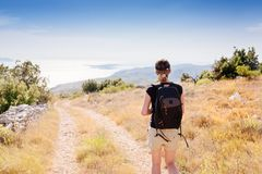 Young woman with backpack at mountain trail. Royalty Free Stock Images