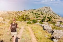 Young woman with backpack at mountain trail. Royalty Free Stock Photos