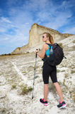 Young woman with backpack in mountains Royalty Free Stock Photo