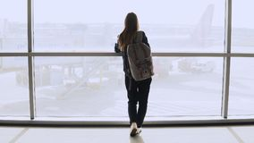 Young woman with backpack near terminal window. Caucasian female tourist using smartphone in airport lounge. Travel. 4K. Young woman with backpack near terminal royalty free stock photo