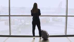 Young woman with backpack near terminal window. Caucasian female tourist using smartphone in airport lounge. Travel. 4K. Stock Photography