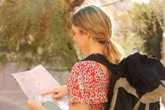 Young woman with backpack pointing to map. Portrait of young woman with backpack pointing to map Royalty Free Stock Images
