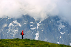 Young woman with backpack in red jacket in mountains Stock Photography