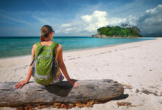 Young woman with backpack relaxing on coast and looking to a isl Royalty Free Stock Photography