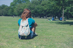 Young woman with backpack relaxing in park Stock Images