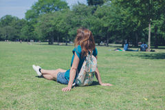 Young woman with backpack relaxing in park Royalty Free Stock Photos