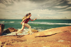 Young woman with a backpack runs on coastal rocks Stock Photos