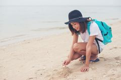 Young woman with backpack sitting on beach and try to make a castle sand. royalty free stock photography