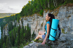 Young woman with backpack sitting on cliff's edge at high mountain.  Royalty Free Stock Images