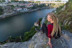 Young woman with backpack sitting on cliff`s edge and looking at the river. Travel. Royalty Free Stock Image