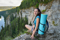 Young woman with backpack sitting on cliff's edge at high mountain