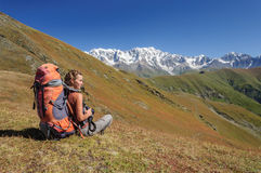 Young woman with backpack sitting on top and looking to mountain Stock Photo