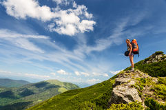 Young woman with backpack standing on cliff Royalty Free Stock Photography