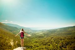 Young woman with backpack standing on cliff edge Stock Photography