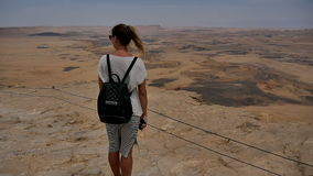 Young woman with backpack standing on cliff`s edge and enjoying the desert view stock video