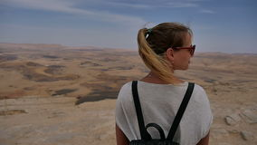 Young woman with backpack standing on cliff`s edge looking at sky and turning around stock video footage