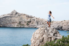 Young woman with backpack standing on cliff's edge Royalty Free Stock Images