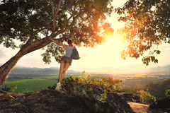 Young woman with backpack standing on the edge of a cliff. Royalty Free Stock Photos