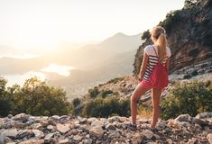 Young woman with backpack standing on the hill Royalty Free Stock Photography