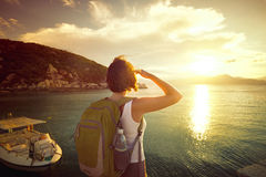 Young woman with backpack standing on the pierce and admiring by Royalty Free Stock Image