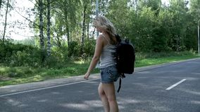 Young woman with backpack and sunglasses crossing the road. Young woman traveler with backpack cross the road on summer day. Woman with backpack in jeans stock video footage