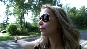 Young woman with backpack and sunglasses hitch hiking car on road. Young woman traveler with backpack hitchhiking on road on summer day. Close up woman with stock video footage