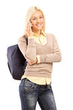Young woman with backpack talking on the phone Royalty Free Stock Images
