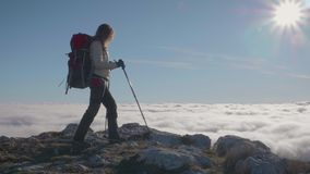 Young Woman with Backpack and Trekking Poles is Hiking on the Edge of Mountain above the Clouds. At sunny day. Steadicam full shot. Slow motion stock video footage