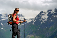 Young woman with backpack and trekking poles in mountains Stock Images