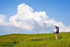 Young woman with backpack and trekking poles Royalty Free Stock Image