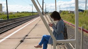 Woman using mobile while waiting for commuter train on the platform. Young woman with backpack using cell phone while waiting for commuter train on the platform stock footage