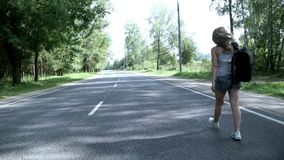 Young woman with backpack walking on the road back view. Young woman traveler with backpack walking on the road on summer day. Woman with backpack in jeans stock video footage