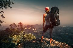 Young woman with backpack. Stands on top of the mountain royalty free stock photos