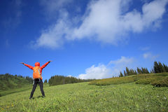 Young woman backpacker hiking on beautiful mountain peak Stock Image