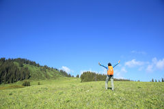Young woman backpacker hiking on beautiful mountain peak Royalty Free Stock Images