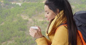 Young woman backpacker savoring her coffee stock video footage