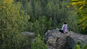 Young woman backpacker sitting on big rock and relax ar sunrise stock video footage
