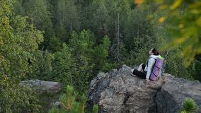 Young woman backpacker sitting on big rock and relax ar sunrise stock video