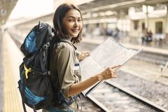 Young woman backpacker smiling and holding map for planning rout stock image