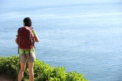 Young woman backpacker standing on seaside mountain Stock Image