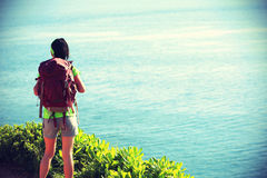 Young woman backpacker standing on seaside mountain Stock Images