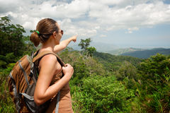 Young woman with backpacker standing on top of the mountain and Royalty Free Stock Image