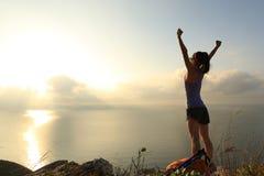 Young woman backpacker at sunrise seaside mountain peak Royalty Free Stock Image