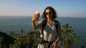 Young woman backpacker taking photo with cellphone on mountain peak stock video
