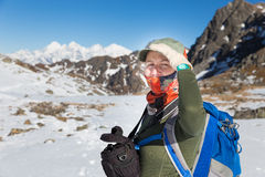 Young woman backpacker tourist standing snow mountains ridge por Royalty Free Stock Images