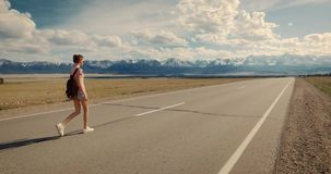 Young woman backpacker walking on road. stock footage