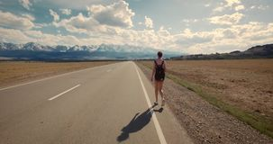 Young woman backpacker walking on road. stock video