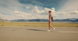 Young woman backpacker walking on road. stock video footage