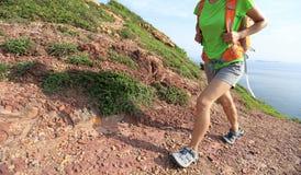 Young woman backpacker walking on  seaside mountain Stock Photos